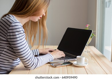 Young woman looking at empy black screen on laptop