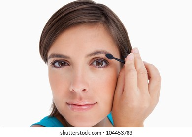 Young woman looking far ahead while putting eyeshadow on her eyelid
