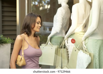 Young woman looking at a fashion store's window.
