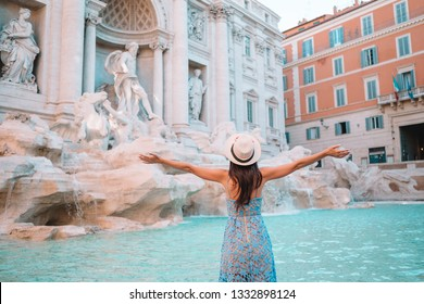 Young woman looking to the Fountain of Trevi during her trip in Rome, Italy. Girl enjoy her european vacation