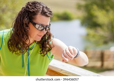 Young woman looking at her activity monitor after exercise