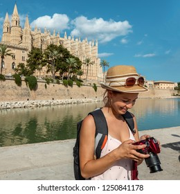 Young woman looking at her camera in front of Palma Cathedral