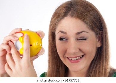 young woman looking at her piggybank
