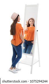 Young woman looking at her reflection in mirror on white background