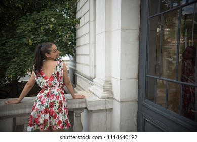 young woman looking at her reflection in window