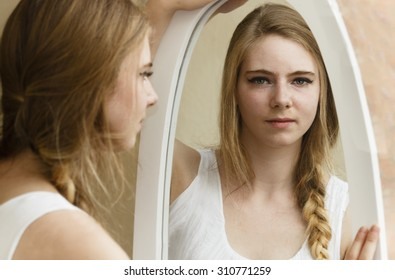 Young woman looking at her reflection in mirror