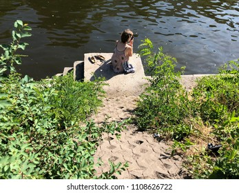 A young woman is looking at her smartphone at the spree-river in Berlin-Kreuzberg. A warm and sunny spring day in Berlin.