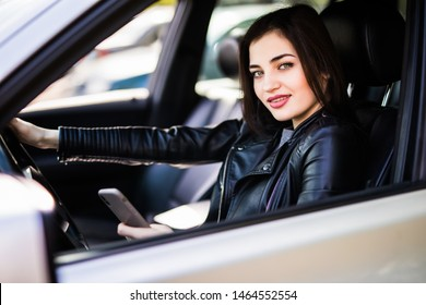 Young woman looking to her smartphone while driving car - rear view, sun shines through front window
