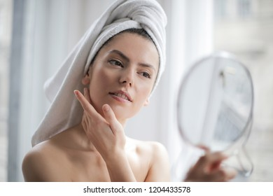 Young woman looking herself in the mirror in the bathroom.