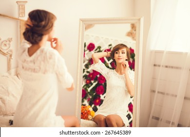 young woman looking at herself in the mirror. gentle portrait