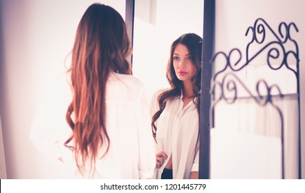 Young woman looking herself reflection in mirror at home. Young woman.