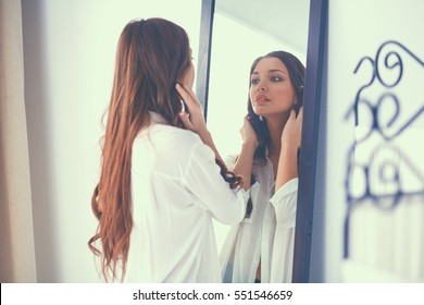 young woman looking herself reflection in mirror at home o46 mirror