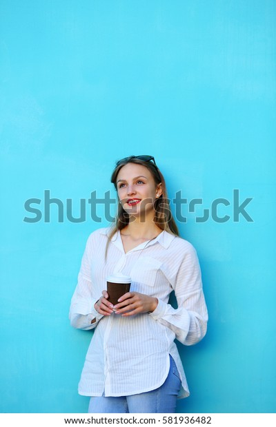 Young woman looking up holding cup coffee