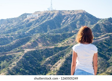 Young woman looking at the Hollywood sign in Los Angeles, California, USA. Dreaming about going to Hollywood.