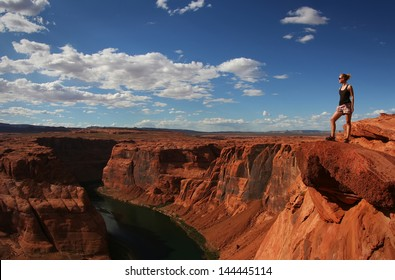 A young woman looking to Horseshoe Bend and Colorado river from the edge of 1000ft canyon in Glen Canyon National Recreation Area, Arizona, USA