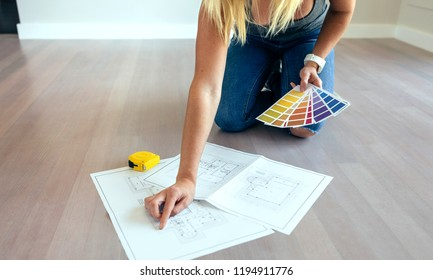 Young woman looking house plans on the floor