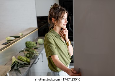 Young woman looking into the fridge, feeling hungry at night