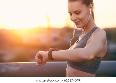 Young woman is looking into the watch after jogging