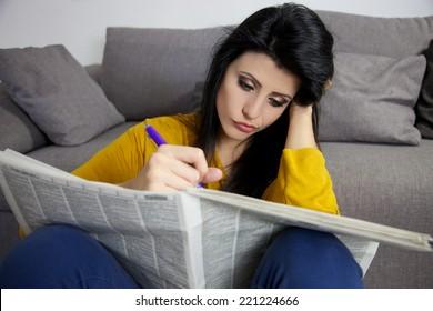 mulher jovem à procura de um emprego no jornal sem sucesso