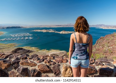 Young woman is looking at the Lake Mead National recreation area as seen from the viewpoint above Hoover Dam in Nevada, United States of America