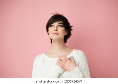 Young woman looking up to the left corner with hands on chest. Happy smiling woman feels grateful, hopes for successful plan realization, believes in success, wishes dream come true, visualizes future