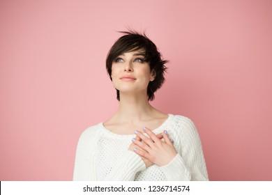 Junge Frau, die an die linke Ecke mit Händen auf der Brust schaut. Fröhlich lächelnde Frau fühlt sich dankbar, hofft auf erfolgreiche Planumstellung, glaubt an Erfolg, Wünsche wahr werden, visualisiert die Zukunft