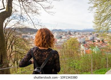 Young woman is looking at the Ljubljana cityscape from Ljubljana castle in Ljubljana, Slovenia
