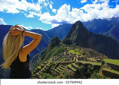 Young woman looking at Machu Picchu. Aerial view of ancient Inca city Machu Picchu, Peru, South America