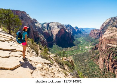 Young woman is looking at the magnificent view from Angel's landing in Zion National park. Travel and adventure concept.
