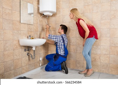 Young Woman Looking At Male Worker Installing Electric Boiler At Bathroom