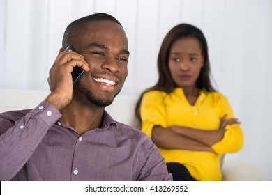 Young Woman Looking At Man Talking On Cellphone At Home