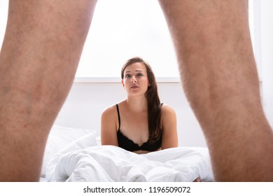 Young Woman Looking At Man's Genital On Bed In Bedroom