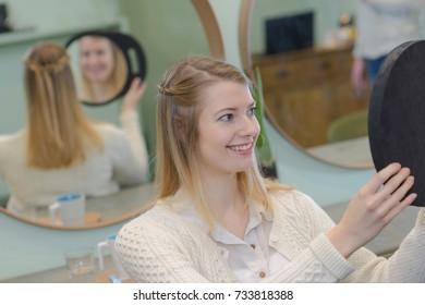 young woman looking in a mirror at the hairdresser