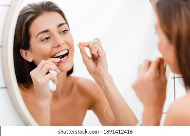 young woman looking in mirror while flossing teeth in bathroom, blurred foreground