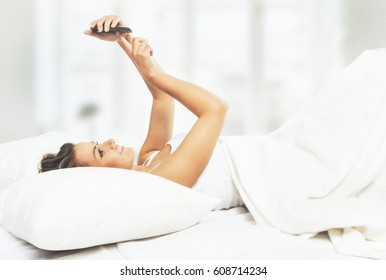 Young woman in looking at mobile phone while lying in bed
