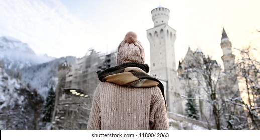 Young woman looking on famous royal castle Neuschwanstein in winter day. Happy winter weekend in the countryside. Vacation in mountains. Alps, Bavaria, Germany (Deutschland)