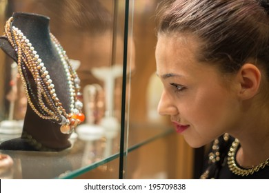 Young woman looking on the jewelry shop window