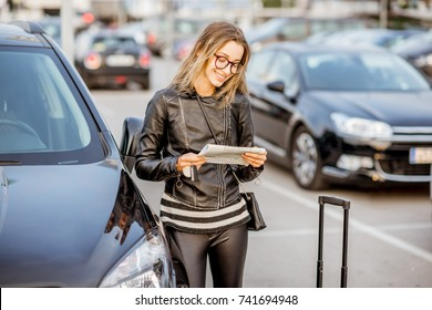 Young woman looking on the rental contract standing outdoors on the airport car parking