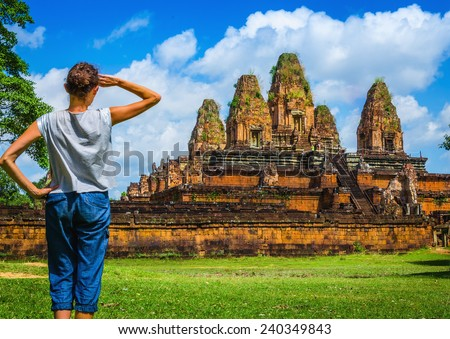 Young woman is looking at one of the temples of Angkor Wat, Siem Reap, Cambodia