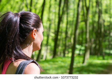 Young woman looking in the opposite direction in a forest