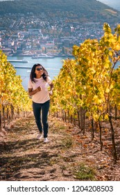 young woman looking out over the wine fields of Rudesheim during fall season harvest view autumn