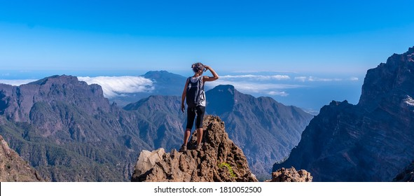 A young woman looking out from the top of the Caldera de Taburiente volcano near Roque de los Muchachos one summer afternoon, La Palma, Canary Islands. Spain