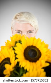 A Young Woman Looking Over A Bunch Of Sunflowers