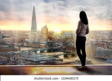 Young woman looking over the City of London at sun set. Future, new business opportunity and business success concept.