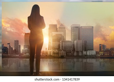 Young woman looking over the City of London business aria with skyscrapers  at sunset. Future, new business opportunity and business success concept. London, UK