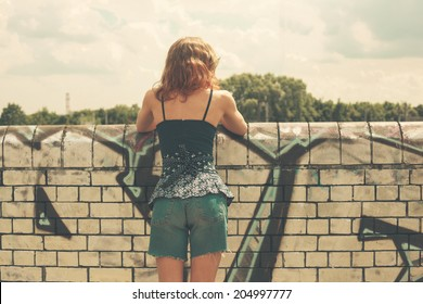 A young woman is looking over a wall outside