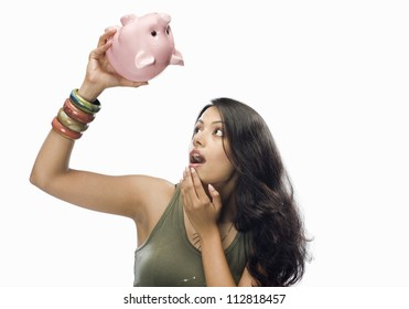 Young woman looking at a piggy bank in shock