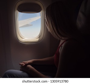 Young woman looking in the porthole in a airplane.