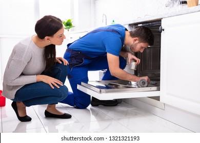 Young Woman Looking At Repairman Repairing Dishwasher In Kitchen