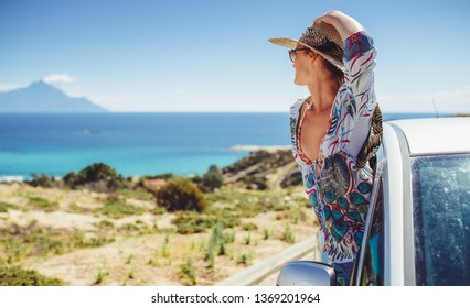 Young woman looking sea from her car